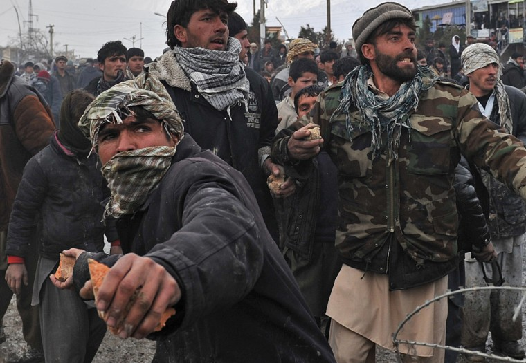 """Afghan youth throw stones toward US soldiers standing at the gate of Bagram airbase during a protest against Koran desecration at Bagram, about 60 kilometres (40 miles) north of Kabul, on February 21, 2012. Afghan protestors firing slingshots and petrol bombs besieged one of the largest US-run military bases in Afghanistan, furious over reports that NATO had set fire to copies of the Koran. Guards at Bagram airbase responded by firing rubber bullets from a watchtower, an AFP photographer said as the crowd shouted """"Allahu akbar, Allahu akbar"""" (God is greater). (Massoud Hossaini/Getty Images)"""