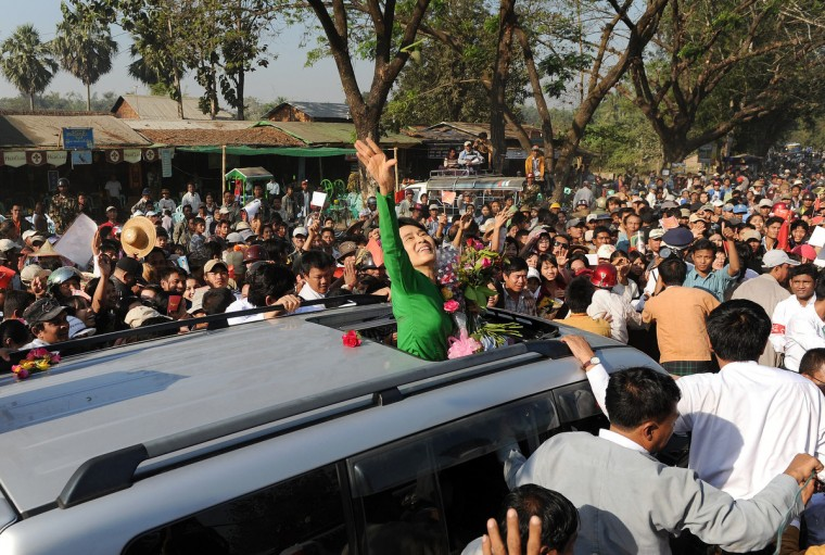 Myanmar opposition leader Aung San Suu Kyi (C) waves as she crosses a crowd of supporters while arriving for a political rally as part of her electoral campaign at a stadium in Pathein, some 200 kms west of Yangon on February 7, 2012. Supporters turned out to greet the Nobel Peace Prize winner on the campaign trip ahead of April 1 by-elections. (Christophe Archambault/Getty Images)