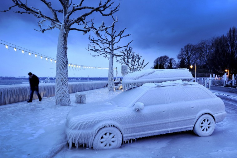 A man walks past an ice covered car on the frozen waterside promenade at Lake Geneva in the city Versoix, near Geneva on early February 5, 2012. The death toll from the vicious cold snap across Europe has risen to more than 260, with the winter misery set to hit thousands of those seeking to escape it as air traffic was hit. (Fabrice Coffrini/Getty Images)