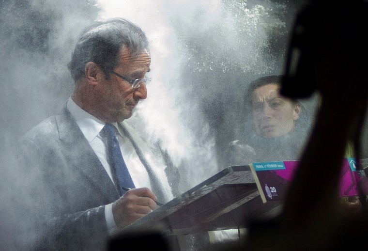 France's opposition Socialist Party (PS) candidate for the 2012 French presidential election Francois Hollande (C) receives flour, thrown by a woman (R) while he was signing a pact on French housing crisis with representatives of the Abb'Pierre Foundation on February 1, 2012 in Paris. (Fred Dufour/Getty Images)
