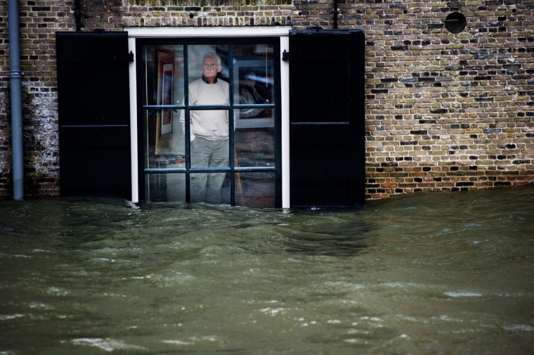 A Dutch local resident, standing in his house, looks to high waters level through his window, in Dordrecht on January 5, 2012. Gale force winds reaching up to 110 kilometres (about 70 miles) an hour as well as heavy rains are expected along the Dutch coast. About a quarter of the country sits below sea level. (Robin Utrecht/Getty Images)