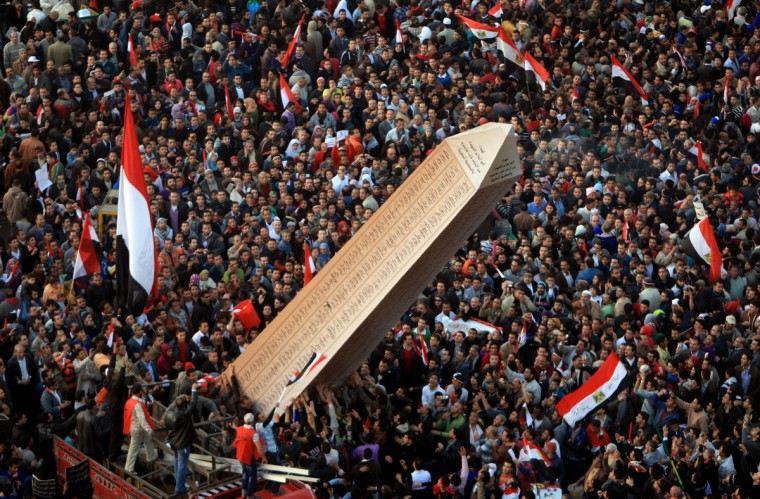 Egyptian protesters carry an obelisk with the names of those killed during last year's uprising, at a huge rally in Tahrir Square on January 25, 2012, marking the first anniversary of the uprising that toppled president Hosni Mubarak as a debate raged over whether the rally was a celebration or a second push for change. (Mahmud Hams/Getty Images)