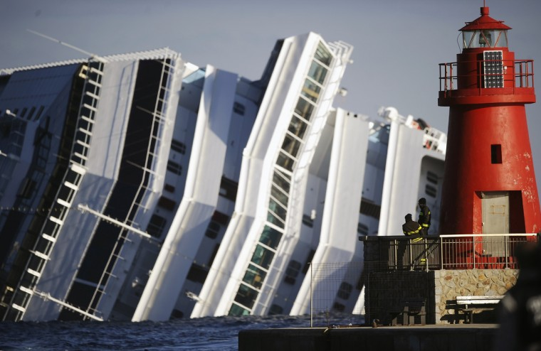 Firemen look at the emerged side of the cruise liner Costa Concordia on January 17, 2012. The Costa Concordia grounded in front of the harbour of Isola del Giglio after hitting underwater rocks on January 13. Rescuers searched for 29 people still unaccounted for from the wreck of a luxury liner off the coast as the arrested captain faced a hearing with investigators. (Filippo Monteforte/Getty Images)