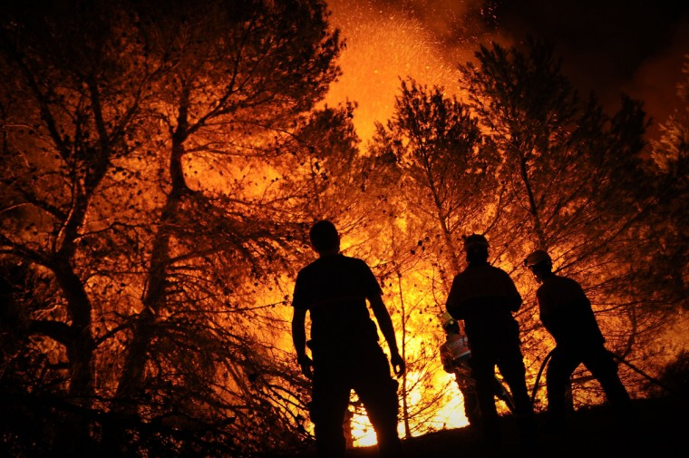 Firefighters of Alcoy and Elda try to extinguish a fire in Torre de Macanes near Alicante, on August 13, 2012. One person was killed and three injured Sunday as firefighters battled wildfires across Spain, authorities said, the latest victims in a sweltering summer of forest blazes. (Pedro Armestre/Getty Images)