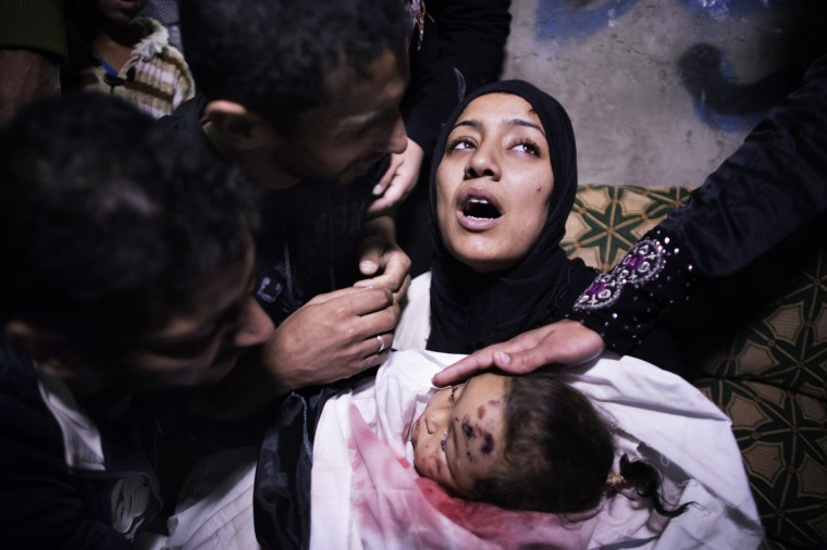The mother of 10-month-old Palestinian girl, Hanen Tafesh, killed the day before in an Israeli air strike, is comforted by her husband and relatives as she mourns before her funeral in Gaza City, on November 16, 2012. Israeli warplanes carried out multiple new air strikes on the Palestinian territory, including several hits on Gaza City, the third day of an intensive campaign which the military has said is aimed at stamping out rocket fire on southern Israel. (Marco Longari/Getty Images)