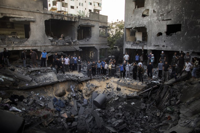 Palestinian men gather around a crater caused by an Israeli air strike on the al-Dallu family's home in Gaza City on November 18, 2012. Israeli air strikes killed at least 18 Palestinians in the bloodiest day so far of its massive air campaign on the Gaza Strip, as diplomatic efforts to broker a truce intensified. (Marco Longari/Getty Images)