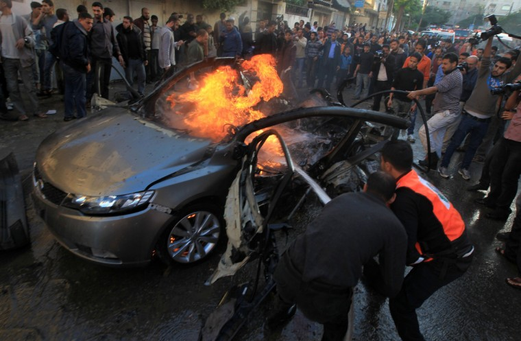 Palestinians extinguish fire from the car of Ahmed Jaabari, head of the military wing of the Hamas movement, the Ezzedin Qassam Brigades, after it was hit by an Israeli air strike in Gaza City on November 14, 2012. The top Hamas commander Ahmed al-Jaabari was killed in an Israeli air strike, medics and a Hamas source told . (Mahmud Hams/Getty Images)