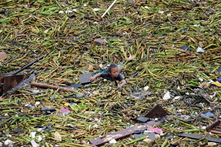 A boy swims amongst the debris as he tries to salvage belongings from destroyed homes hit after two barges smashed into an informal settler area in Manila on July 30, 2012, when strong winds and rains due to Tropical Storm Saola hit the capital. At least one person was killed and millions were left without power on July 30, as Tropical Storm Saola brought heavy rains to large parts of the Philippines, the government said. (Ted Aljibe/Getty Images)