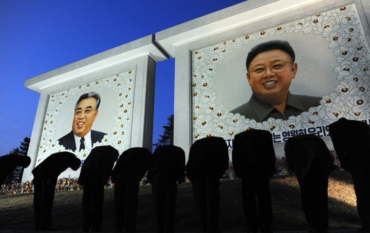 North Koreans pay their respects in front of two portraits, one of founding leader Kim Il-Sung (L) and the other of his son Kim Jong-Il in Pyongyang on April 9, 2012. North Korea is counting down to the 100th anniversary of its founder's birth on April 15 with top-level meetings and a controversial rocket launch scheduled in coming days to bolster his grandson's credentials. (Pedro Ugarte/Getty Images)
