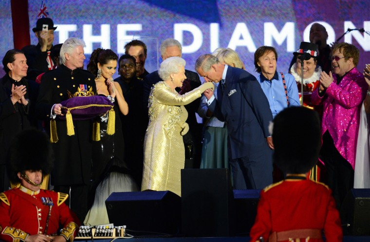 Prince Charles, Prince of Wales, kisses the hand of Britain's Queen Elizabeth II on stage as British singers Paul McCartney (3R) and Elton John (R) and other performers look on after the Jubilee concert at Buckingham Palace in London on June 4, 2012. A chain of more than 4,200 beacons began to flare across the globe Monday to mark Queen Elizabeth II's diamond jubilee, with the last to be lit by the monarch at a star-studded concert at Buckingham Palace. (Leon Neal/Getty Images)
