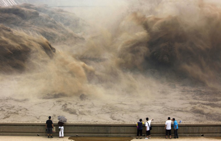 Visitors watch giant gushes of water released from the Xiaolangdi dam to clear up the sediment-laden Yellow river and to prevent localized flooding, in Jiyuan, central China's Henan province. China is hit by big downpours every summer often causing fatalities as seen in 2010, which saw the nation's worst flooding in a decade leaving more than 4,300 people dead or missing. (Getty Images)