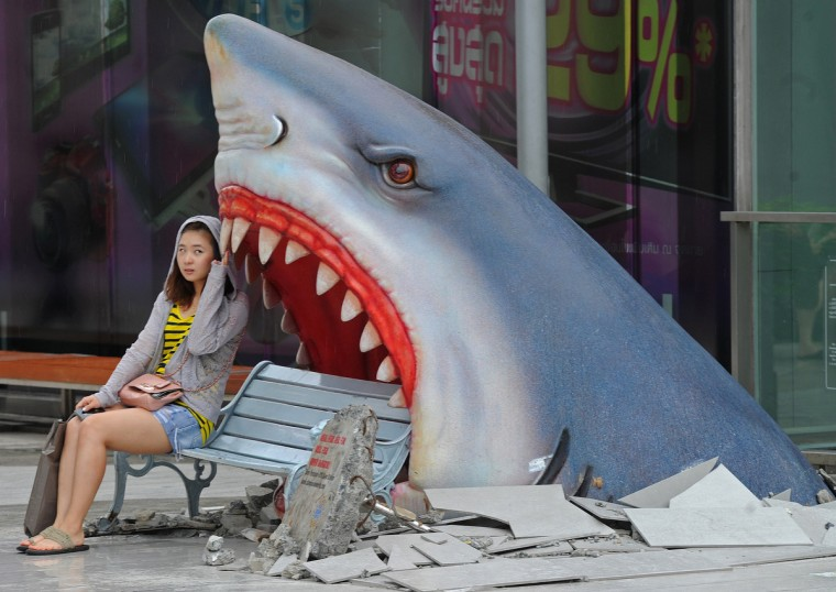 """A foreign tourist sits next to a large art display of a shark displayed at a shopping mall in Bangkok on July 9, 2012. Thailand is a tourist magnet but its image as the """"Land of Smiles"""" has been tested in recent years by deadly political unrest, devastating floods and more recently a bungled bomb plot involving Iranian suspects. (Pornchai Kittiwongsakul/Getty Images)"""