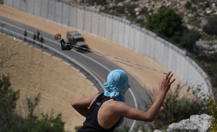 A Palestinian youth readies to sling a stone at Israeli soldiers as they patrol along the controversial Israeli built separation barrier during clashes close to the village of Bilin, just west of the city Ramallah, in the occupied Israeli West Bank, on April 13, 2012. (Abbas Momani/Getty Images)