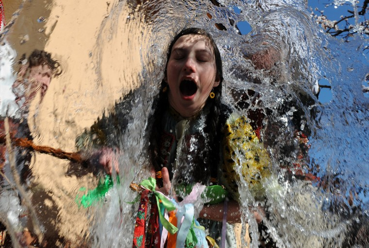 Young Slovaks dressed in traditional costumes throw a bucket of water at a girl as part of Easter celebrations in the village of Trencianska Tepla, 145 km north of Bratislava on April 9, 2012. Slovakia's men splash women with water and hit them with a willow to symbolize youth, strength and beauty for the upcoming spring season. (Samuel Kubani/Getty Images)