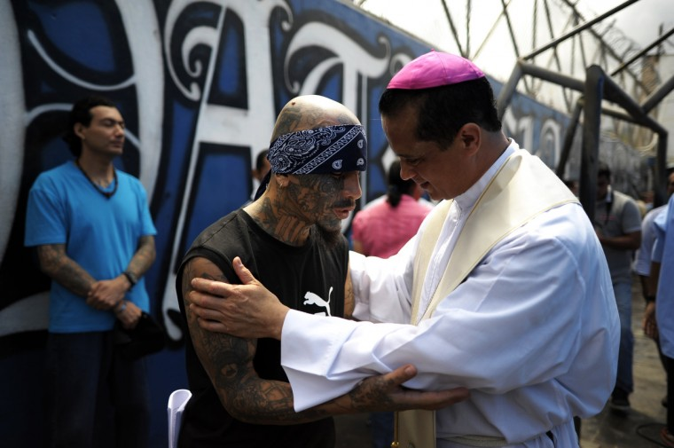 Catholic priest Fabio Colindres (L) speaks with a member of Mara Salvatrucha gang during a mass at the prison of Ciudad Barrios, 160 km east of San Salvador, El Salvador on June 19, 2012. Inmates participated in a mass to celebrate 100 days after a truce was declared between gangs and the Salvadorean goverment. (Jose Cabezas/Getty Images)