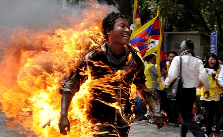 Tibetan exile Jamphel Yeshi, 27, runs as he is engulfed in flames after he set himself on fire during a protest in New Delhi on March 26, 2012. A Tibetan exile set himself on fire on Monday during a rally in New Delhi to protest against an upcoming visit to India by Chinese President Hu Jintao, police said. (Getty Images)