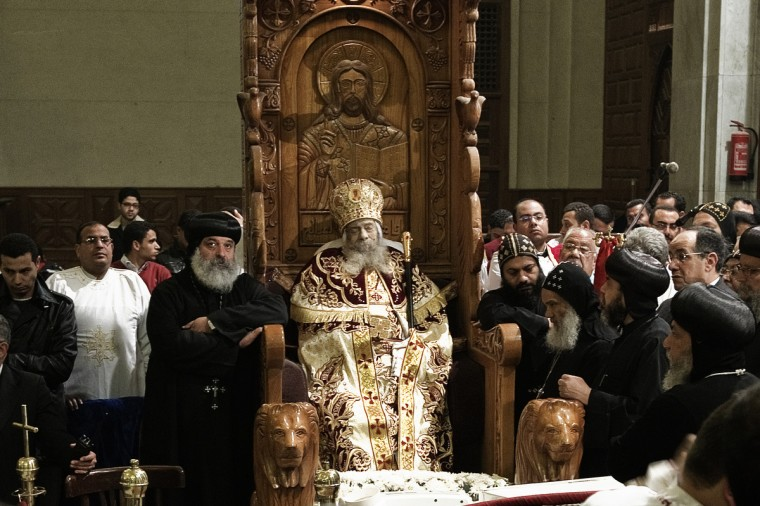 Egyptian Coptic priests gather around the body of Pope Shenuda III, the spiritual leader of the Middle East's largest Christian minority, sitting dressed in formal robes on a wooden throne at the Saint Mark's Coptic Cathedral in Cairo's al-Abbassiya district on March 19, 2012. Pope Shenuda died at the age of 88, after a long battle with illness and based on his wishes he will be buried on March 20, at St. Bishoy monastery in Wadi Natrun in the Nile Delta where he spent his time in exile after a dispute with late president Anwar Sadat. (Gianluigi Guercia/Getty Images)