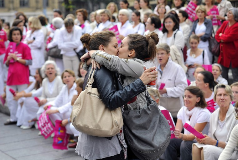 """Two women kiss in front of people taking part in a demonstration called by the """"Alliance VITA"""" association against gay marriage and adoption by same-sex couples on October 23, 2012 in Marseille, southeastern France. France on October 10 named October 31 as the date when a draft law authorizing gay marriage will be approved by government ministers, amid mounting opposition to the proposed legislation. (Gerard Julien/Getty Images)"""