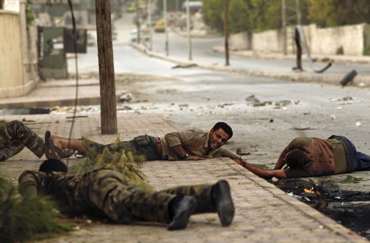 Members of the Al-Baraa bin Malek batalion, part of the Free Syria Army's Al-Fatah brigade, duck to the ground as they pull a man (R) who was shot by a sniper twice in the Bustan al-Basha district of the northern city of Aleppo on October 20, 2012. Due to the risk of being shot by the sniper, no one was able to rescue the man who eventually ran towards rebels, only to be shot by the sniper a second time. Rebels then pulled him and rushed him to a hospital, though it is not known if he survived. Three civilians were shot on this main road in the space of three hours by the same sniper. (Javier Manzano/Getty Images)