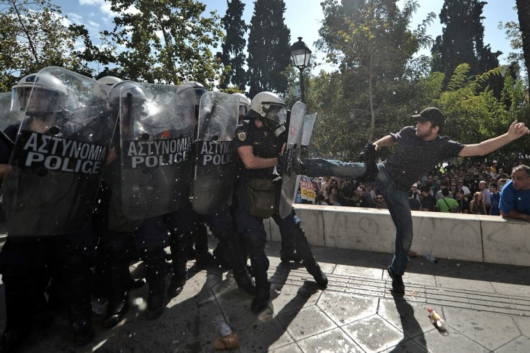 A demonstrator clashes with riot police during a 24-hour strike in Athens on October 18, 2012. Greek riot police fired tear gas to disperse protesters at an anti-austerity rally in Athens held during a national general strike as EU leaders were to tackle the eurozone crisis at a summit. The protesters had broken through a police line outside luxury hotels on central Syntagma Square and scattered groups of youths later attacked police with stones and firebombs, an AFP reporter said. (Aris Messinis/Getty Images)