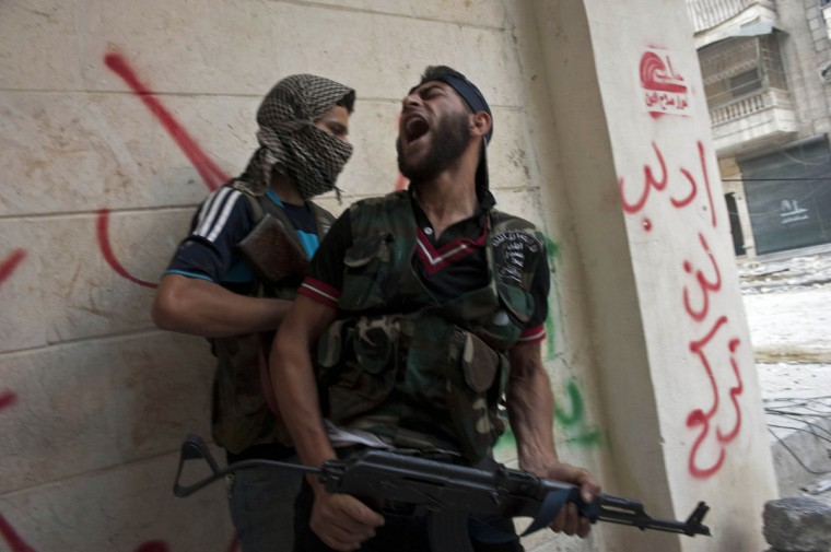 Free Syrian Army fighters take cover as they exchange fire with regime forces in the Salaheddin neighborhood of Syria's northern city of Aleppo on August 22, 2012. At least 12 people were killed in a raid on a district of Damascus, while fighter jets and artillery pummeled the city of Aleppo and rebels claimed seizing parts of a town on the Iraqi border, a watchdog said. (James Lawler Duggan/Getty Images)