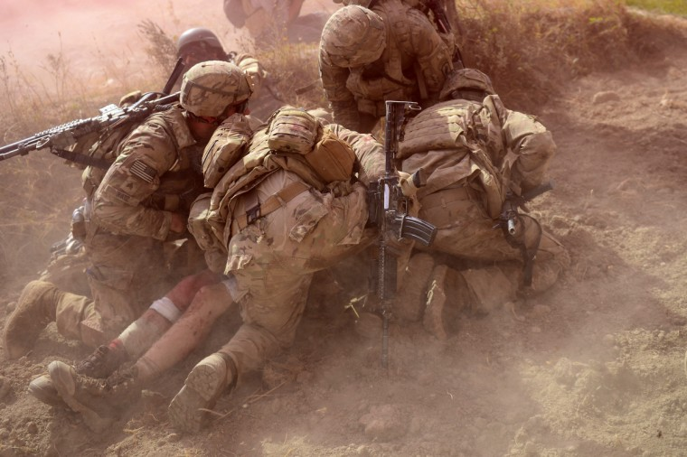 US Army soldiers attached to 2nd platoon, C troop, 1st Squadron (Airborne), 91st U.S Cavalry Regiment, 173rd Airborne Brigade Combat Team operating under NATO sponsored International Security Assistance Force (ISAF) protect a wounded comrade from dust and smoke flares after an Improvised Explosive Device (IED) blast during a patrol near Baraki Barak base in Logar Province on October 13, 2012. The soldier, 21 year-old Private Ryan Thomas from Oklahoma suffered soft tissue damage and after surgery in Afghanistan was scheduled to be evacuated to Germany. After 11 years of war, 2,135 US soldiers dead, their Afghan colleagues turning on them, and widespread predictions the conflict will end in failure, coalition forces could be forgiven for suffering a dip in morale. But commanders and soldiers on the ground insist the challenges are bringing them closer together, even if the outcome of the war is uncertain and the perception of what constitutes success has changed. (Munir uz Zaman/Getty Images)