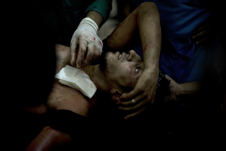 A rebel fighter is brought to the Dar al-Shifa hospital in the northern city of Aleppo to be treated for his wounds on October 1, 2012, as fighting in Syria's second largest city between rebel forces and government troops continues. (Zac Baillie/Getty Images)