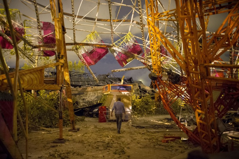 A man walks under the wreckage of a fair ride after a tornado ripped through a funfair in Gandia, near Valencia on September 29, 2012. Ten people, including a young girl and an elderly woman, have died in Spain as a result of floods brought on by downpours, regional officials said. (Pedro Armestre/Getty Images)