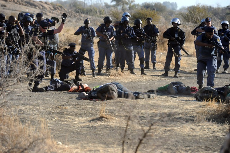 Police surround fallen miners after they opened fire during clashes near a platinum mine in Marikana on August 16, 2012. Hundreds of workers armed with machetes, sticks and metal rods had gathered on a hillside near the mine, defying police orders to disperse. Several people were lying on the ground, some bleeding from wounds, after the crowd fled, according to an AFP reporter. (Getty Images)