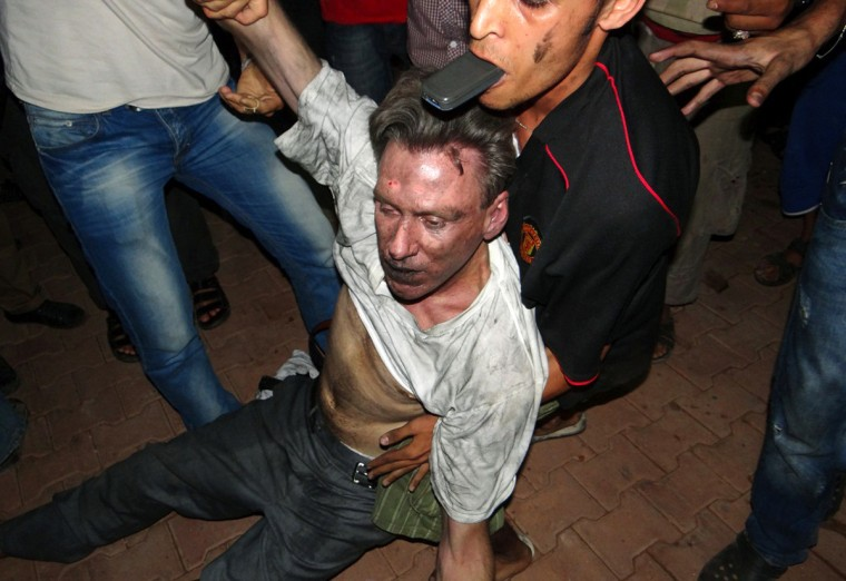 Libyan civilians help an unconscious man, identified by eyewitnesses as US ambassador to Libya Chris Stevens, at the US consulate compound in Benghazi in the early hours of September 12, 2012, following an overnight attack on the building. Stevens and three of his colleagues were killed in an attack on the US consulate in the eastern Libyan city by Islamists outraged over an amateur American-made Internet video mocking Islam, less than six months after being appointed to his post. (Getty Images)
