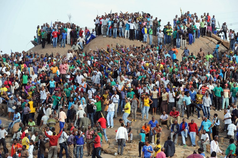 People gather on a hill in Marikana on August 23, 2012 after attending a memorial service for the 44 people killed in a wildcat strike at Lonmin's Marikana mine. Lonmin and nearby Impala Platinum closed for the day as workers prepared for memorials, including the main national service at Marikana where police gunned down 34 miners a week ago after deadly clashes had already claimed 10 people. The service at Lonmin will be the focal point during a day of mourning that will stretch across the country, as many of the victims were migrant workers whose bodies have already returned to their home villages. (Getty Images)