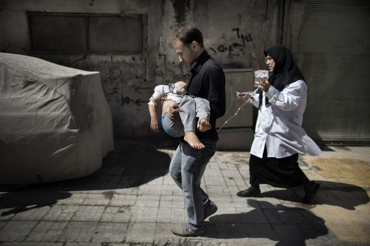 A Syrian man carries his wounded daughter outside a hospital in the northern city of Aleppo on September 18, 2012. Syrian troops shelled several districts in Aleppo and clashed with rebels, as Damascus ally Iran proposed a simultaneous halt to the violence and a peaceful solution to the conflict. (Marco Longari/Getty Images)