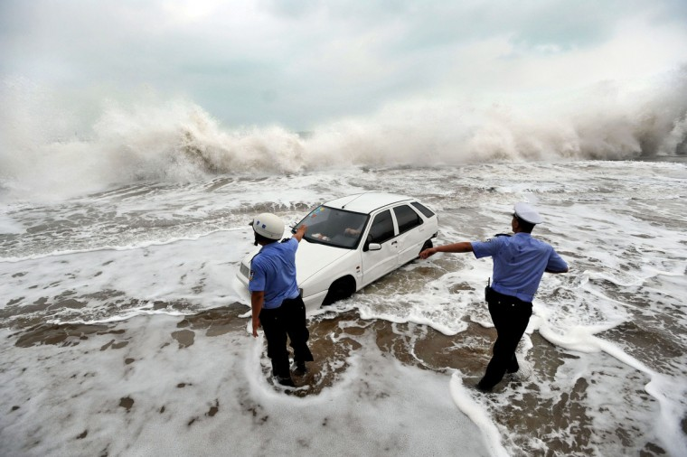 Police try to help remove a car surrounded by water after its owner parked it on the bank to watch waves brought on by Typhoon Bolaven in Qingdao, in northeast China's Shandong province. Typhoon Bolaven -- the strongest storm to hit South Korea for almost a decade -- left a trail of death and damage in southwestern and south-central regions of the Korean peninsula on August 28, and crossed into China early on August 29. (Getty Images)