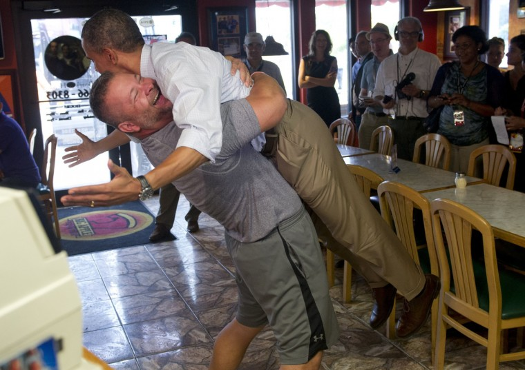 US President Barack Obama is picked up by Scott Van Duzer, owner of Big Apple Pizza and Pasta Italian Restaurant during a visit to the restaurant in Fort Pierce, Florida, September 9, 2012, during the second day of a 2-day bus tour across Florida. (Saul Loeb/Getty Images)