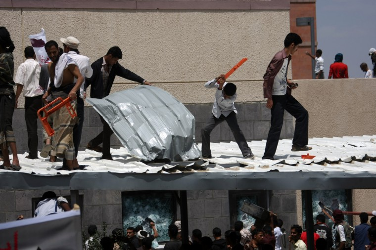 Yemeni protesters try to break through the US embassy in Sanaa during a protest over a film mocking Islam on September 13, 2012. Yemeni forces managed to drive out angry protesters who stormed the embassy in the Yemeni capital with police firing warning shots to disperse thousands of people as they approached the main gate of the mission. (Mohammed Huwais/Getty Images)