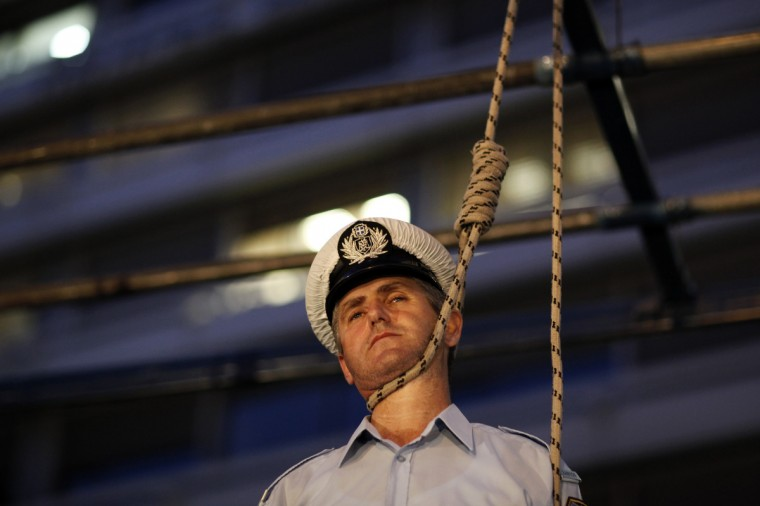 A police officer stands in a mock gallows outside the Finance Ministry during a protest against budget cuts in Athens, on September 6, 2012. Nearly 2,000 policemen, coast guards and firefighters continued their protests against planned salary cuts, as security forces summoned from around the country attended an evening demonstration on Thursday in Athens.The measures reportedly include a 3.5-billion-euro slash to pensions, health cuts worth 1.47 billion euros and a 517-million-euro cut to defense. (Kostas Tsironis/Getty Images)