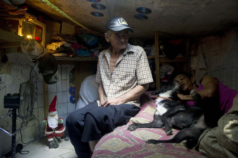 Colombian Miguel Restrepo (L), rests with his wife Maria Garcia and their dog on a bed inside a sewer. (Raul Arboleda/Getty Images)