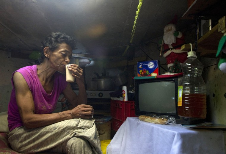 Colombian Maria Garcia drinks coffee inside her sewer home. (Raul Arboleda/Getty Images)