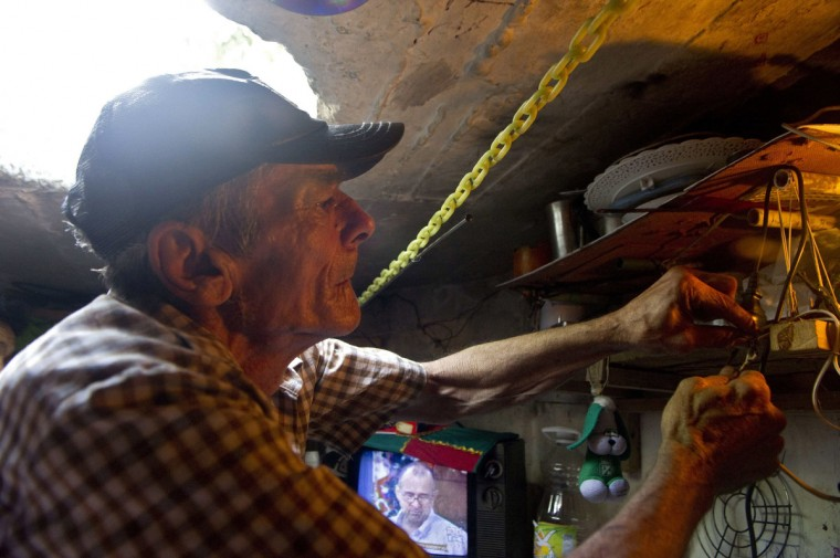 Colombian Miguel Restrepo repairs the electricity installation inside the sewer where he lives. (Raul Arboleda/Getty Images)