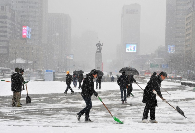 Public officials clear snow at the Gwanghwamun Square in Seoul. It was the first fall of snow this year in the capital. (Kim Jae-Hwan/Getty Images)