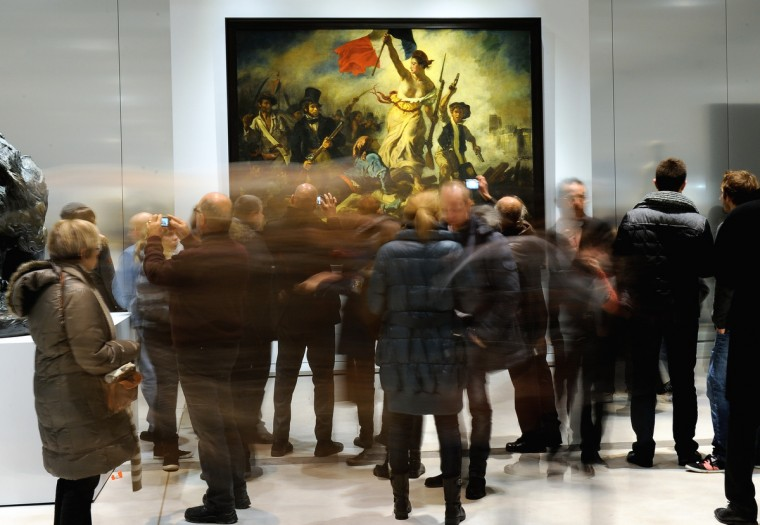 "People stand in front of the Eugene Delacroix masterpiece ""La Liberte guidant le Peuple"" (Liberty leading the people) at the Louvre Museum on the first day of its opening to the public in Lens, northern France. The Louvre museum opened a new satellite branch among the slag heaps of a former mining town Tuesday in a bid to bring high culture and visitors to one of France's poorest areas. Greeted by a group of former miners in overalls and hardhats, President Francois Hollande inaugurated today the Japanese-designed glass and polished-aluminum branch of the Louvre in the northern city of Lens. The 150 million euro ($196 million) project was 60 percent financed by regional authorities in the Nord-Pas-De-Calais region, on the English Channel and the border with Belgium. (Phillippe Huguen/Getty Images)"