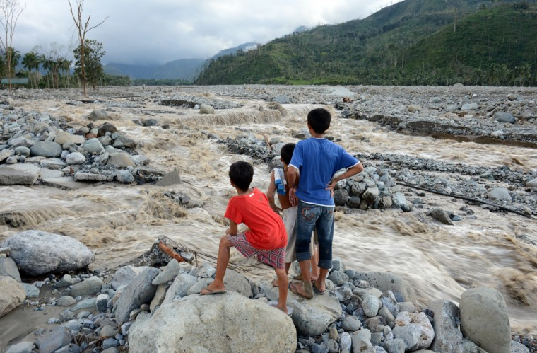 Children look at the a damaged road destroyed by flash floods at the height of Typhoon Bopha in the village of Andap, New Bataan town, Compostela Valley province. (Ted Aljibe/Getty Images)