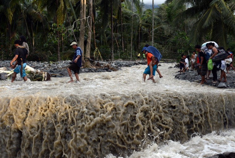 Residents cross a damaged road destroyed at the height of Typhoon Bopha in the village of Andap,New Bataan town, Compostela Valley province. (Ted Aljibe/Getty Images)
