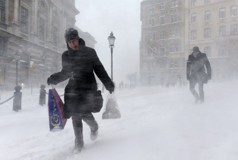 People struggle against wind and drifting snow in Stockholm. Forecasters have issued a class 2 storm warning for central and southern Sweden, saying that Stockholm may face up to 30 centimeters of snow in the next 24 hours. (Anders Wiklund/Getty Images)