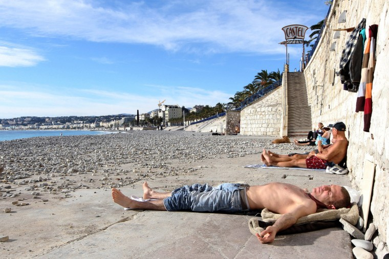 People take a sunbath on the beach in Nice, southeastern France. (Jean Christophe Magnenet/Getty Images)