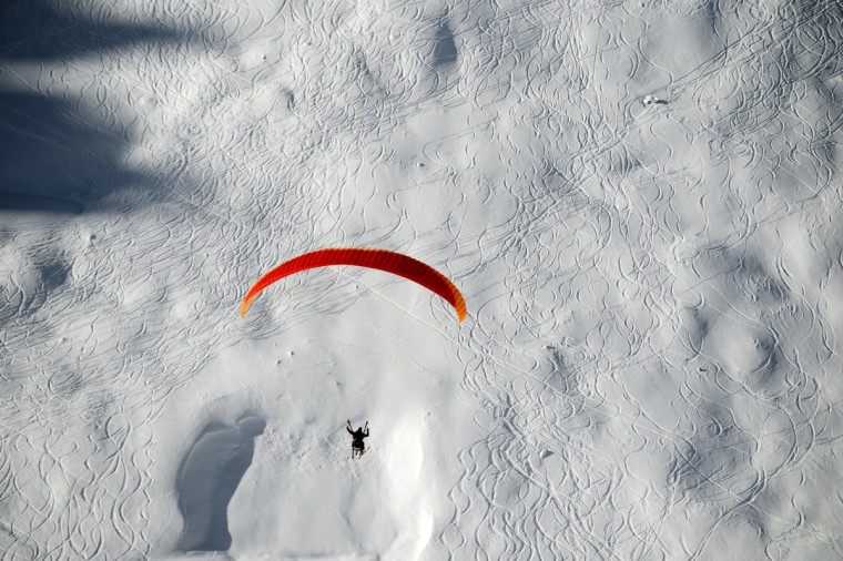 A paraglider glides over Tignes, French Alps. Recent snowfalls have encouraged skiers to hit the slopes and the Tignes authorities have opened certain slopes early. (Philippe Desmazes/Getty Images)