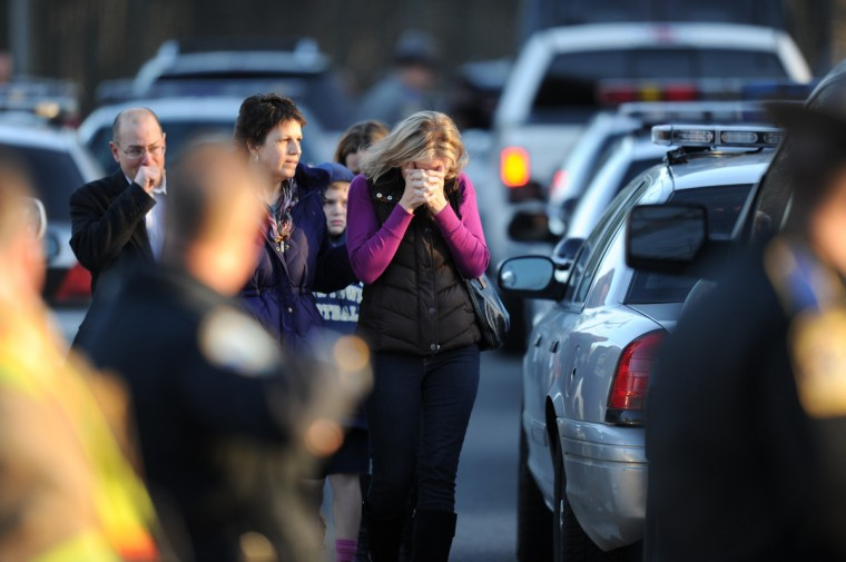 Residents grieve following a shooting at Sandy Hook Elementary School in Newtown, Connecticut. At least 26 people, including 20 young children, were killed when a gunman assaulted the school and another body was found dead at a second linked crime scene, police said. (Don Emmert/Getty Images)