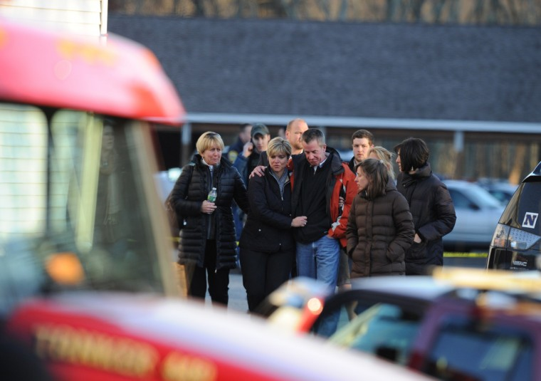 Grieving residents gather following a shooting at Sandy Hook Elementary School in Newtown, Connecticut. At least 26 people, including 20 young children, were killed when a gunman assaulted the school. (Don Emmert/Getty Images)