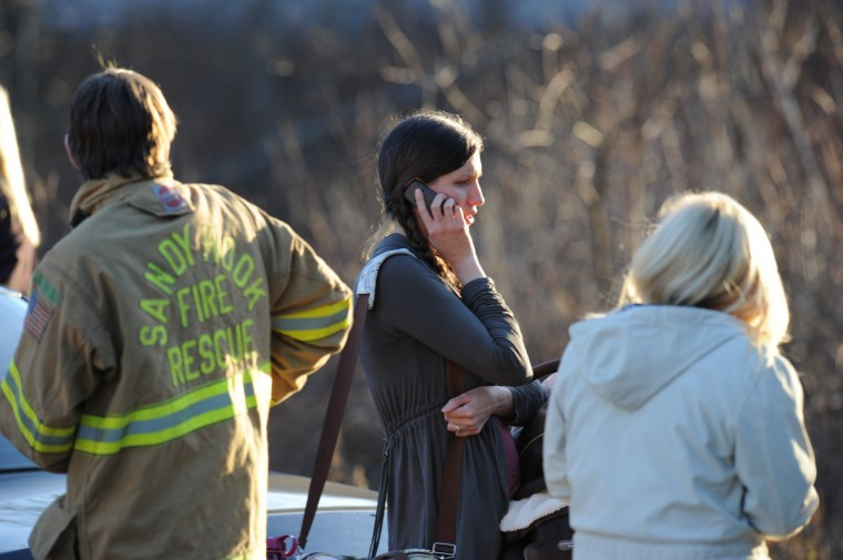 An unidentified woman makes a phone call at the aftermath of a school shooting at a Connecticut elementary school that brought police swarming into the leafy neighborhood, while other area schools were put under lock-down, police and local media said. (Don Emmert/Getty Images)