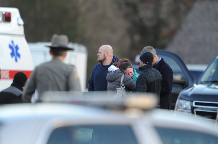 Police stand before grieving residents following a shooting at Sandy Hook Elementary School in Newtown, Connecticut. (Don Emmert/Getty Images)